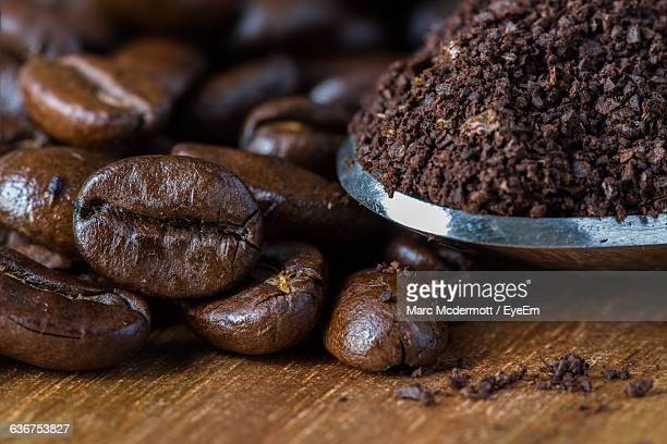 close-up of roasted coffee beans on table - café moulu photos et images de collection