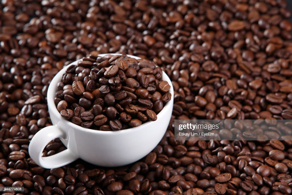 Close-Up Of Roasted Coffee Beans With Cup : Stock Photo