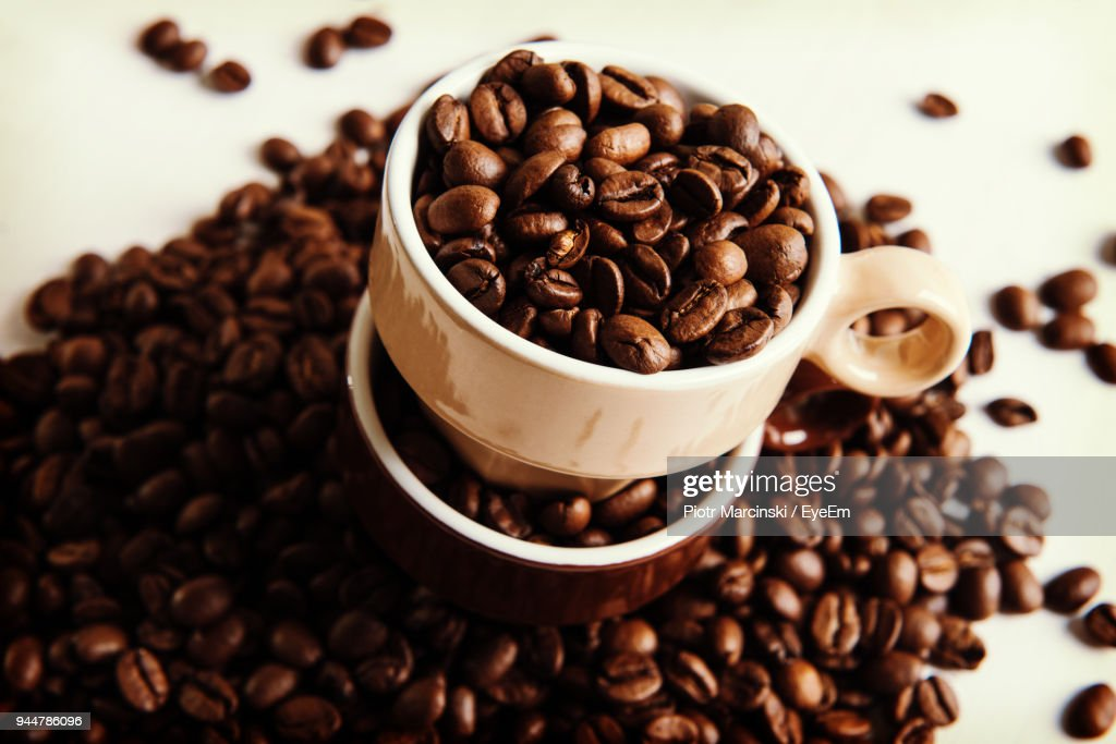 Close-Up Of Roasted Coffee Beans With Cups On Table : Stock Photo