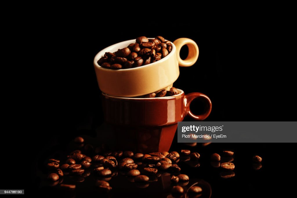 Close-Up Of Roasted Coffee Beans With Cups Over Black Background : Stock Photo