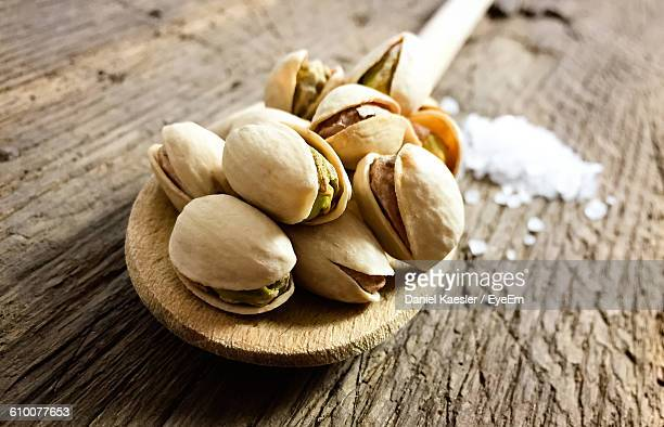 Close-Up Of Roasted Pistachios On Wooden Spoon