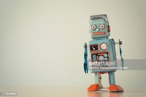 close-up of robot on table against wall - robot stock pictures, royalty-free photos & images