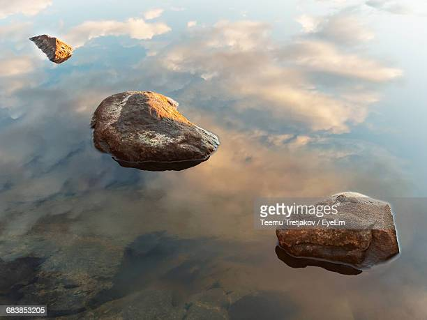 close-up of rock on lake against sky - teemu tretjakov stock pictures, royalty-free photos & images