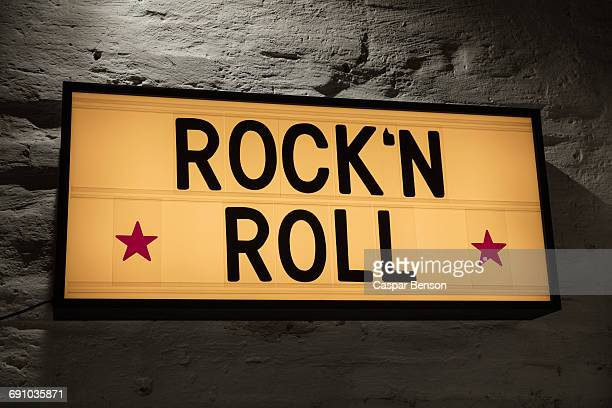 close-up of rockn roll signboard against gray wall - early rock & roll stock pictures, royalty-free photos & images