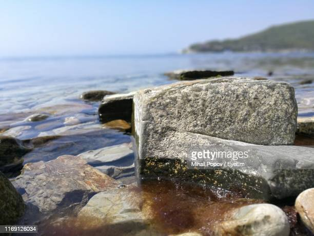 close-up of rocks by sea against sky - 巨礫 ストックフォトと画像
