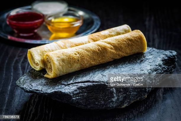 Close-Up Of Rolled Crepe Suzettes On Black Stone At Table