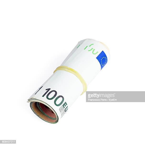 Close-Up Of Rolled Up One Hundred Euro Banknote Against White Background