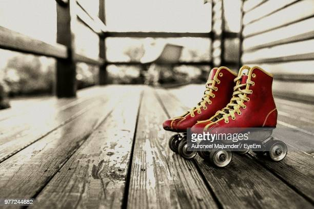 close-up of roller skates on floorboard - floorboard stock photos and pictures