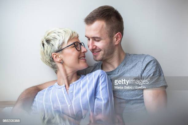 close-up of romantic couple sitting by wall at home - marija mauer stock-fotos und bilder