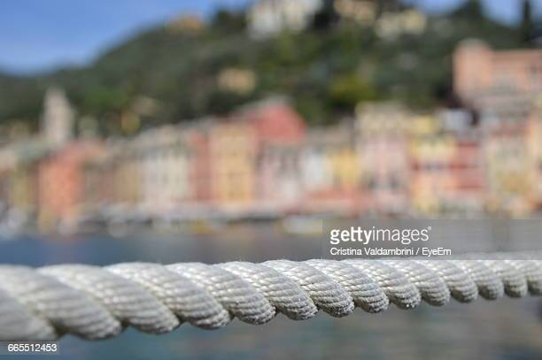Close-Up Of Rope By Lake Against Buildings