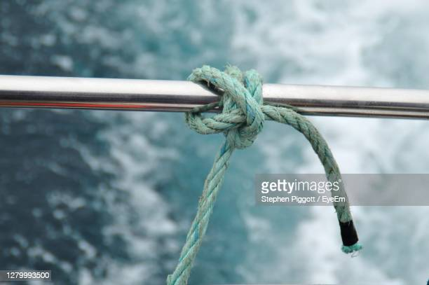close-up of rope tied on metal rail on boat - sailing stock pictures, royalty-free photos & images