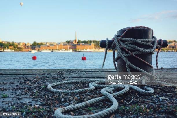 close-up of rope tied to harbor against sky - moored stock pictures, royalty-free photos & images