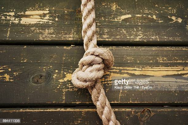 Close-Up Of Rope With Tied Knot Against Wood