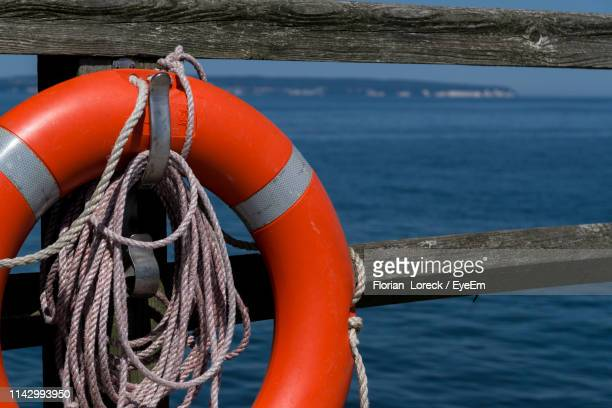 close-up of ropes and life belt on railing by sea - buoy stock photos and pictures