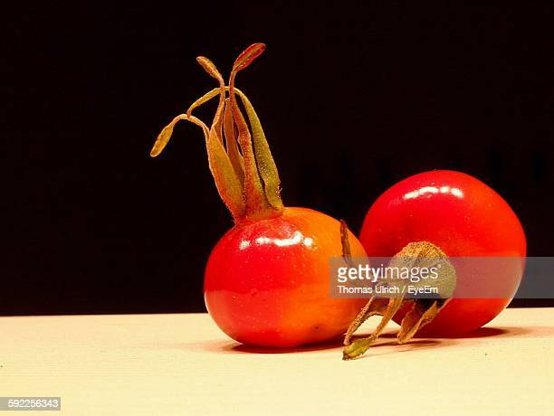 Close-Up Of Rose Hips On Table Against Black Background