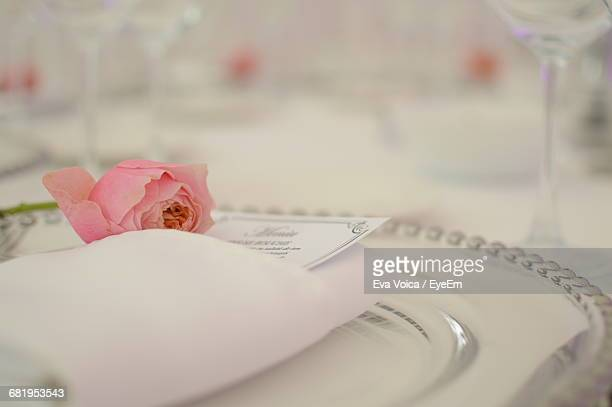 Close-Up Of Rose With Invitation Card On Plate At Wedding Reception