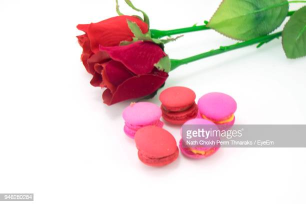 Close-Up Of Roses And Macaroons Over White Background
