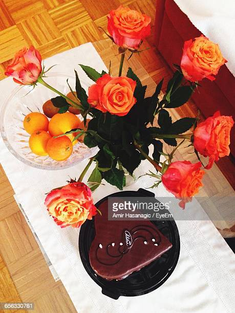 Close-Up Of Roses In Vase By Chocolate Cake On Table During Valentine Day