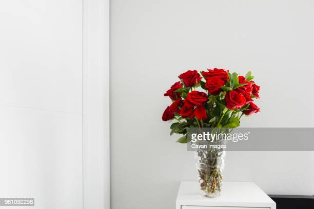 close-up of roses in vase on table by wall at home - mazzo di rose foto e immagini stock