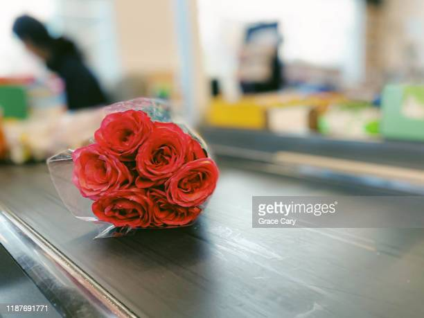 close-up of roses on supermarket conveyor belt - conveyor belt stock pictures, royalty-free photos & images