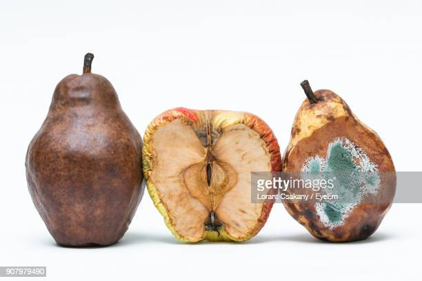 close-up of rotten fruits against white background - rot stock pictures, royalty-free photos & images