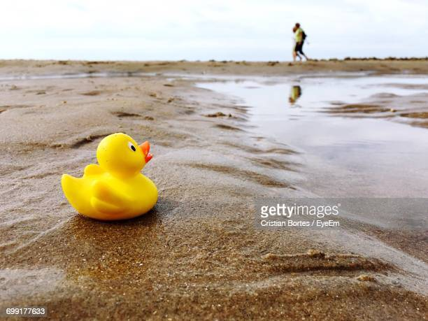 Close-Up Of Rubber Duck At Sandy Beach