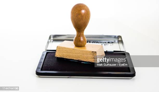 close-up of rubber stamp on ink pad against white background - timbro foto e immagini stock