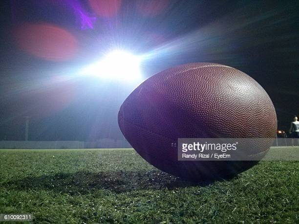 Close-Up Of Rugby Ball On Field Against Illuminated Floodlight At Night