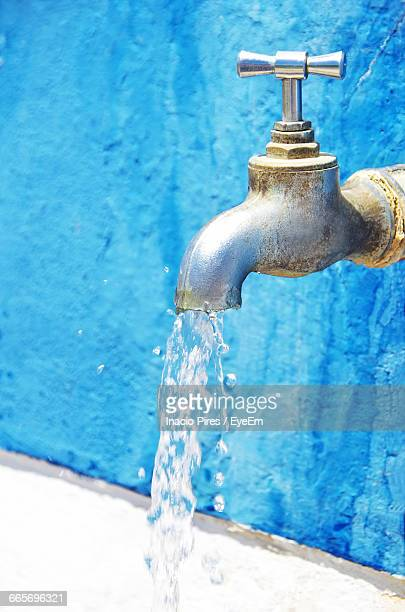 close-up of running tap against wall - 水流 ストックフォトと画像