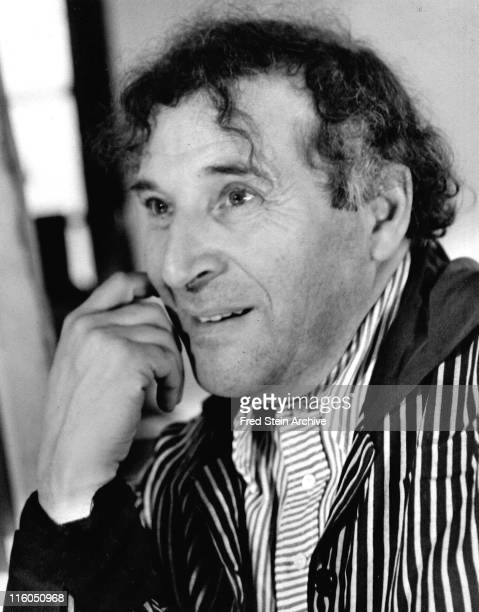 Close-up of Russian-born French artist Marc Chagall with his hand on his cheek, dressed in a striped shirt and jacket, New York, New York, 1945.