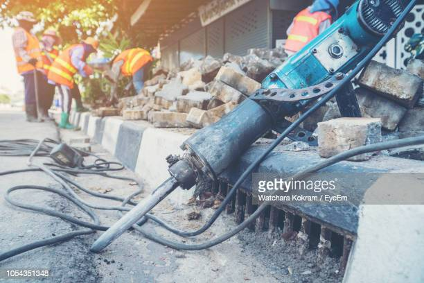 close-up of rusty jackhammer on road at construction site - road construction stock photos and pictures