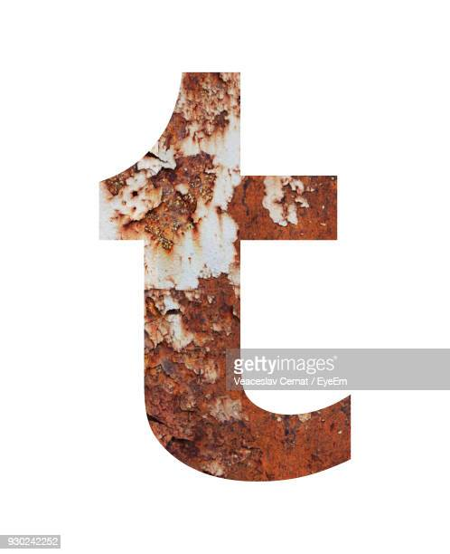 Close-Up Of Rusty Letter T Against White Background