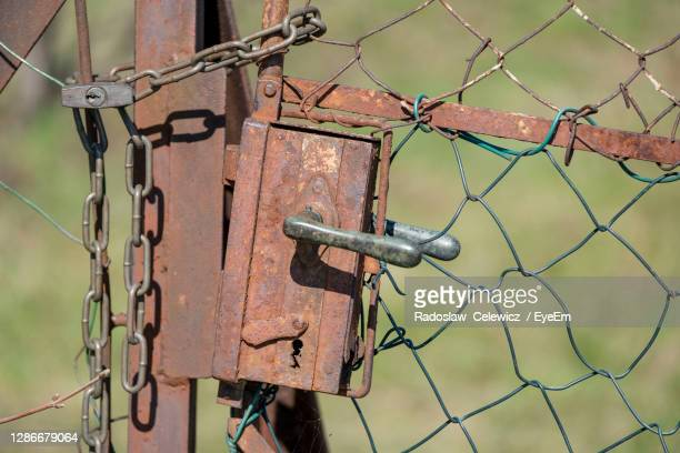 close-up of rusty lock on chainlink fence - weathered stock pictures, royalty-free photos & images