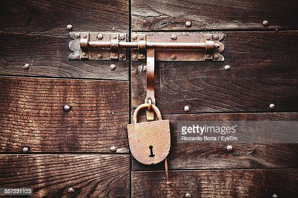 close-up of rusty lock on wooden door - padlock stock photos and pictures