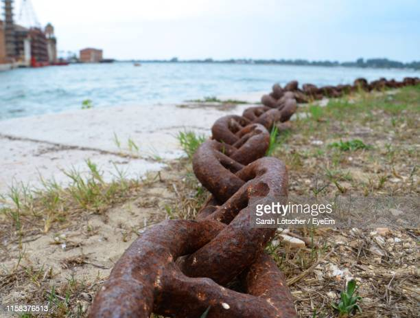 close-up of rusty metal chain at harbor - sarah hardy stock pictures, royalty-free photos & images