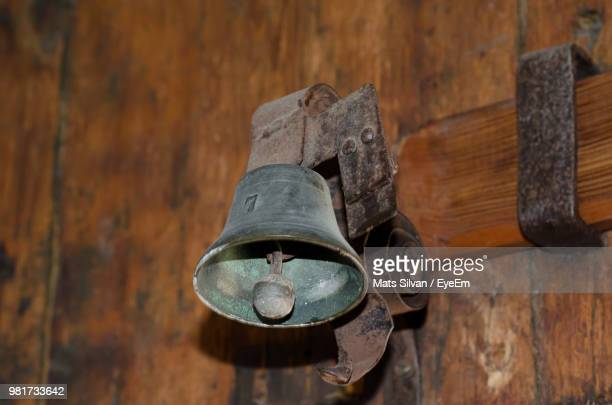 Close-Up Of Rusty Metallic Bell Hanging On Wooden Wall