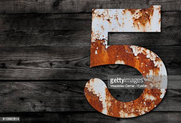 Close-Up Of Rusty Number 5 On Table