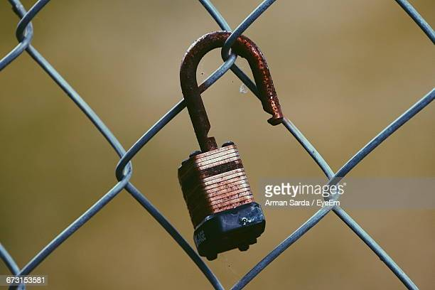 Close-Up Of Rusty Padlock On Chainlink Fence