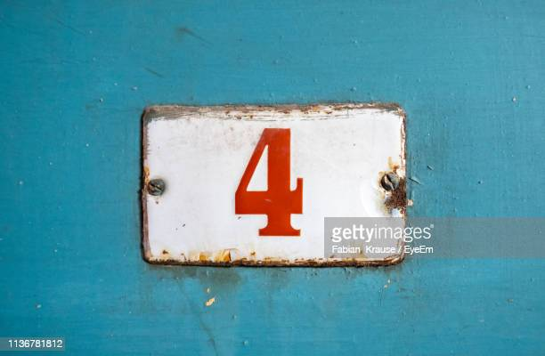close-up of rusty sign with number 4 on blue wall - imperfection stock pictures, royalty-free photos & images