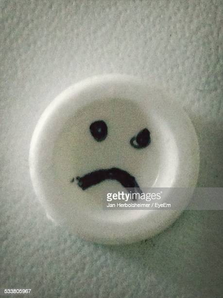 Close-Up Of Sad Smiley Face Drawn On Circle Stuck To Wall