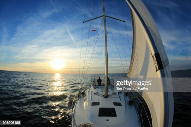 Close-Up Of Sailboat Sailing On Sea Against Sky During Sunset