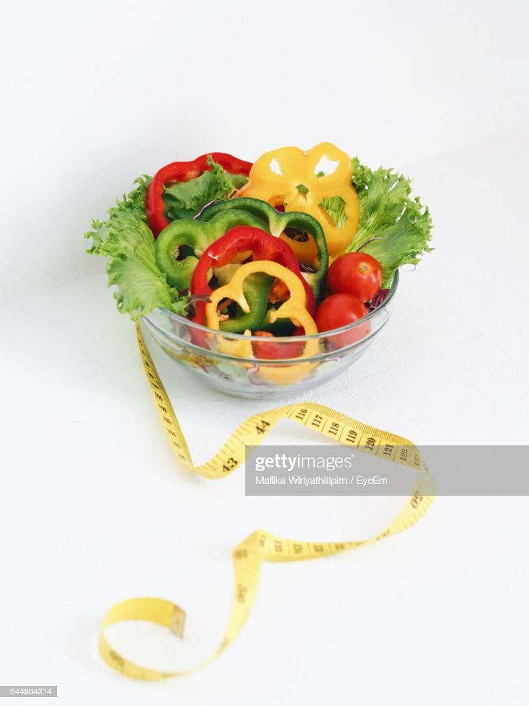 Close-Up Of Salad Bowl And Tape Measure Against White Background : Stock Photo