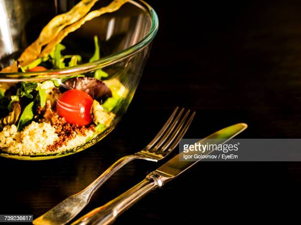 close-up of salad served in bowl by fork on table - igor golovniov stock pictures, royalty-free photos & images