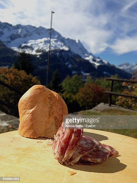 Close-Up Of Salami On Table Against Snowed Landscape