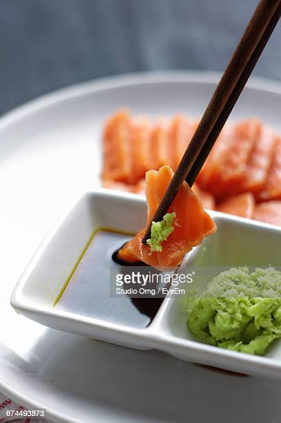 close-up of salmon wasabi dipped in soy sauce - 醤油 ストックフォトと画像