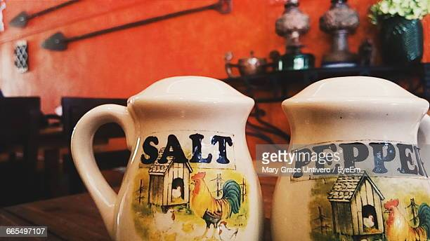 Close-Up Of Salt And Pepper Shakers On Table At Restaurant