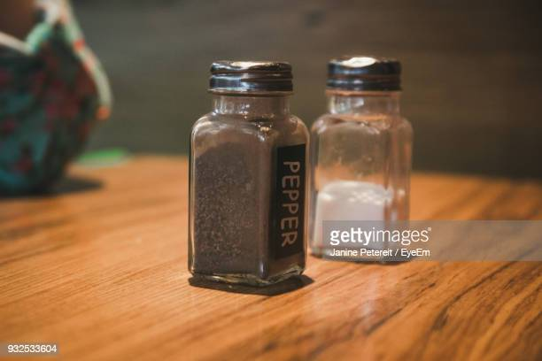 Close-Up Of Salt And Pepper Shakers On Wooden Table