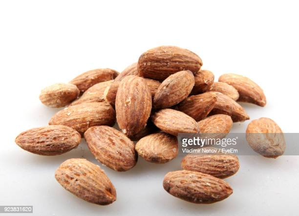 close-up of salted almonds against white background - salted stock photos and pictures