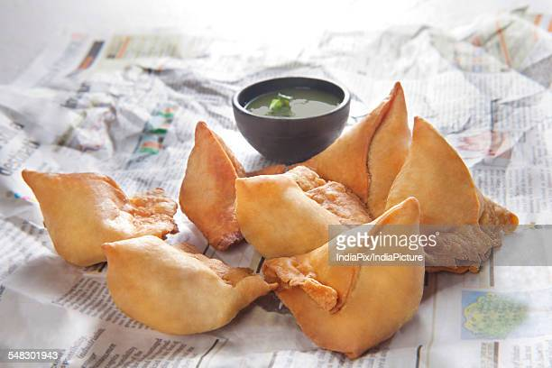 Close-up of samosas on a piece paper with chutney