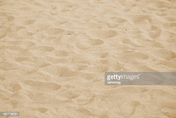A close-up of sand on a beach with numerous footprints
